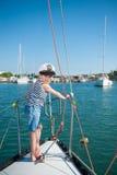 O capitão de sorriso do rapaz pequeno a bordo do barco luxuoso durante o oceano cruza Foto de Stock