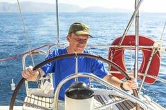 O capitão do homem novo no leme controla o iate da navigação esporte Fotos de Stock