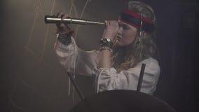 O capitão do pirata no navio está olhando ao redor através do telescópio pequeno, 4k vídeos de arquivo