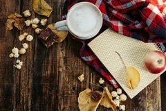 O cappuccino quente com pipoca, maçã, bolos, folhas no velho corteja Fotografia de Stock Royalty Free