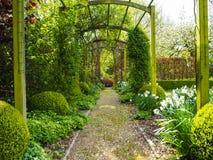 O caramanchão da entrada ao jardim durante a mola, flanqueada pelo whi Imagens de Stock Royalty Free