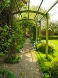 O caramanchão da entrada ao jardim durante a mola, flanqueada pelo whi Fotografia de Stock