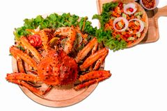 O caranguejo de rei do Alasca cozinhado serviu com a salada vegetal isolada no fundo branco Pés de caranguejo do Alasca vermelhos imagens de stock