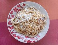 O carbonara dos espaguetes em um prato com flores projeta fotografia de stock royalty free