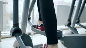 O cardio- treinamento, pé do ser humano vai em instrutores elípticos no centro de esportes video estoque