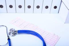 O cardiograma com estetoscópio médico e o doutor revestem na tabela Fotos de Stock