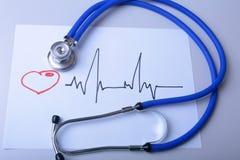 O cardiograma com estetoscópio médico e o doutor revestem na tabela fotografia de stock royalty free