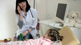 O cardiologista remove o cardiograma do coração no hospital, criança na recepção do doutor pediatra, médico recebe pacientes video estoque