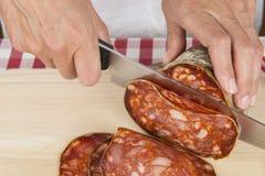 O carniceiro que corta uma salsicha espanhola chamou o morcon Imagens de Stock Royalty Free