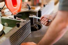 O carpinteiro ajusta o cortador Imagens de Stock Royalty Free