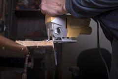 O carpinteiro amador usa a ferramenta da serra de vaivém imagens de stock royalty free