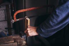 O carpinteiro amador usa a mão viu imagem de stock royalty free
