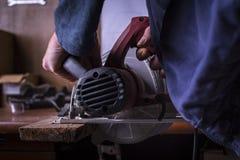 O carpinteiro amador usa o poder viu fotografia de stock