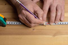 O carpinteiro com um lápis marca a placa para a mobília feita da madeira imagem de stock