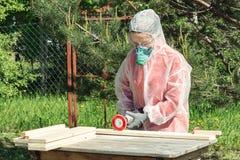 O carpinteiro da mulher no respirador, nos óculos de proteção e nos macacões trata uma placa de madeira com um moedor de ângulo imagens de stock