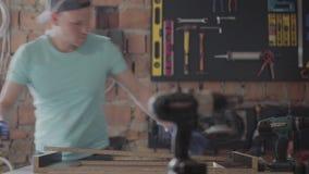 O carpinteiro especializado do retrato que corta uma parte de madeira em sua oficina da carpintaria, usando uma circular viu com  video estoque