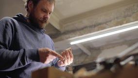 O carpinteiro especializado profissional mói o pente de madeira da barba com papel de risco artesão handmade 4 K video estoque