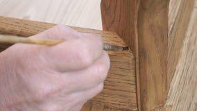 O carpinteiro está cobrindo a tabela pela laca vídeos de arquivo