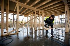 O carpinteiro fêmea Cutting Wood Using bonde viu na construção fotos de stock