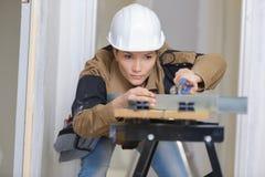 O carpinteiro fêmea no trabalho viu sobre o banco fotografia de stock royalty free