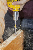 O carpinteiro fura o furo da trava da fechadura da porta, usando o bocado de pá fotografia de stock