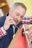 O carpinteiro instala a porta usando a chave de fenda fotografia de stock