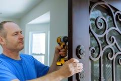 O carpinteiro instala um fechamento resistente seguro na porta do metal imagem de stock