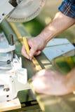 O carpinteiro Marking On Wood que usa a régua na tabela viu fotos de stock