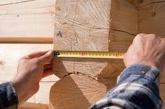 O carpinteiro mede registros de madeira Foto de Stock Royalty Free