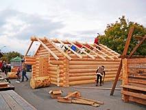 O carpinteiro monta o quadro de madeira com as vigas comuns no telhado da cabine Imagens de Stock