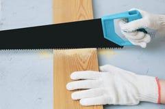 O carpinteiro nas luvas está vendo uma placa de madeira com uma serra imagens de stock