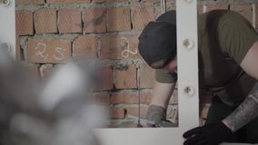 O carpinteiro no tampão preto e luvas com tatuagens nos braços que põem a colagem sobre o quadro de madeira para o espelho O trab video estoque