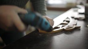 O carpinteiro prende vertentes ao suporte de madeira para medalhas filme