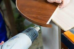O carpinteiro profissional no trabalho seca uma árvore por um close-up industrial profissional da ferramenta do secador de cabelo fotografia de stock