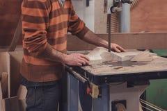 O carpinteiro que corta a madeira na fita viu imagem de stock royalty free