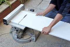 O carpinteiro que corta uma placa da melamina branca com poder do disco viu Fotografia de Stock Royalty Free