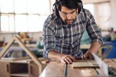 O carpinteiro que faz cortes da precisão à madeira que usa uma tabela viu imagem de stock