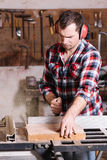 O carpinteiro que trabalha em um zumbido bonde viu o corte de algumas placas Foto de Stock Royalty Free