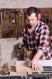 O carpinteiro que trabalha em um zumbido bonde viu o corte de algumas placas Fotografia de Stock Royalty Free