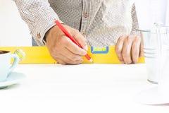 O carpinteiro que trabalham com equipamento nivelado e a madeira escrevem em sua mão na tabela branca Fotografia de Stock