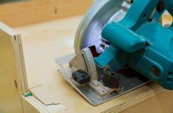 O carpinteiro que usa o eletro circular viu o corte da mobília da cozinha imagem de stock royalty free