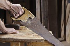 O carpinteiro que vê uma placa com uma madeira da mão viu Fotografia de Stock Royalty Free