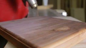 O carpinteiro seca a placa coberta com o secador da construção do mordente vídeos de arquivo