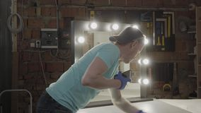 O carpinteiro terminou fazer ampolas no espelho para o cliente e limpar a superfície As luzes est?o ligada Conceito vídeos de arquivo