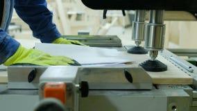 O carpinteiro trabalha em uma máquina de furo Contratado na produção de mobília de madeira vídeos de arquivo