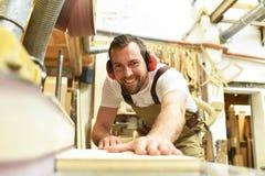O carpinteiro trabalha em uma obra de carpintaria - oficina para o woodworking e o sawi imagem de stock royalty free