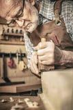 O carpinteiro usa uma plaina Fotos de Stock
