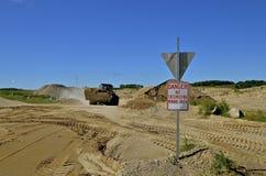 O carregador da parte frontal leva a areia em uma área de mineração fotos de stock