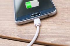 O carregador do telefone celular e de bateria cabografa na mesa de escritório fotos de stock royalty free