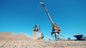 O carregador mecânico relocating o cascalho no local de mineração filme